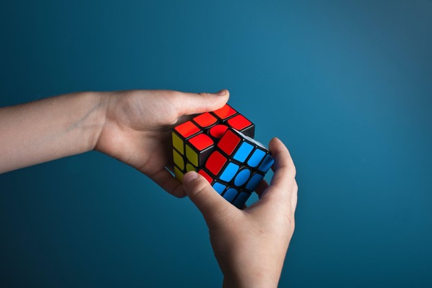 someone is playing with rubix cube, with coaching business can find what works for them