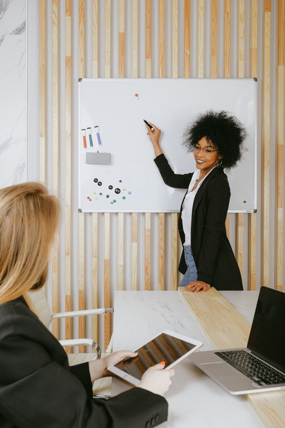 two women, one stands in front of whiteboard coaching the other one that is sitting with tablet in hand